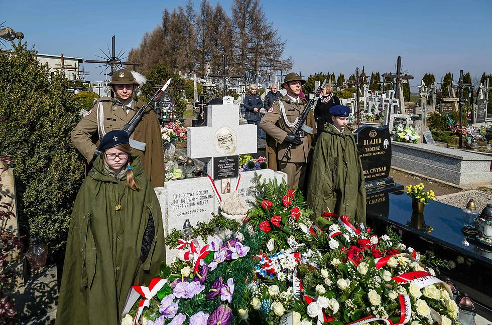 Men lays a wreath during a ceremony at the grave of The Ulma family (Photo: AFP)