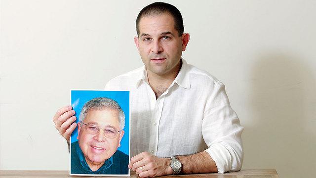 """מיכה אבני עם תמונת אביו, ריצ'רד לייקין ז""""ל (צילום: דנה קופל) (צילום: דנה קופל)"""