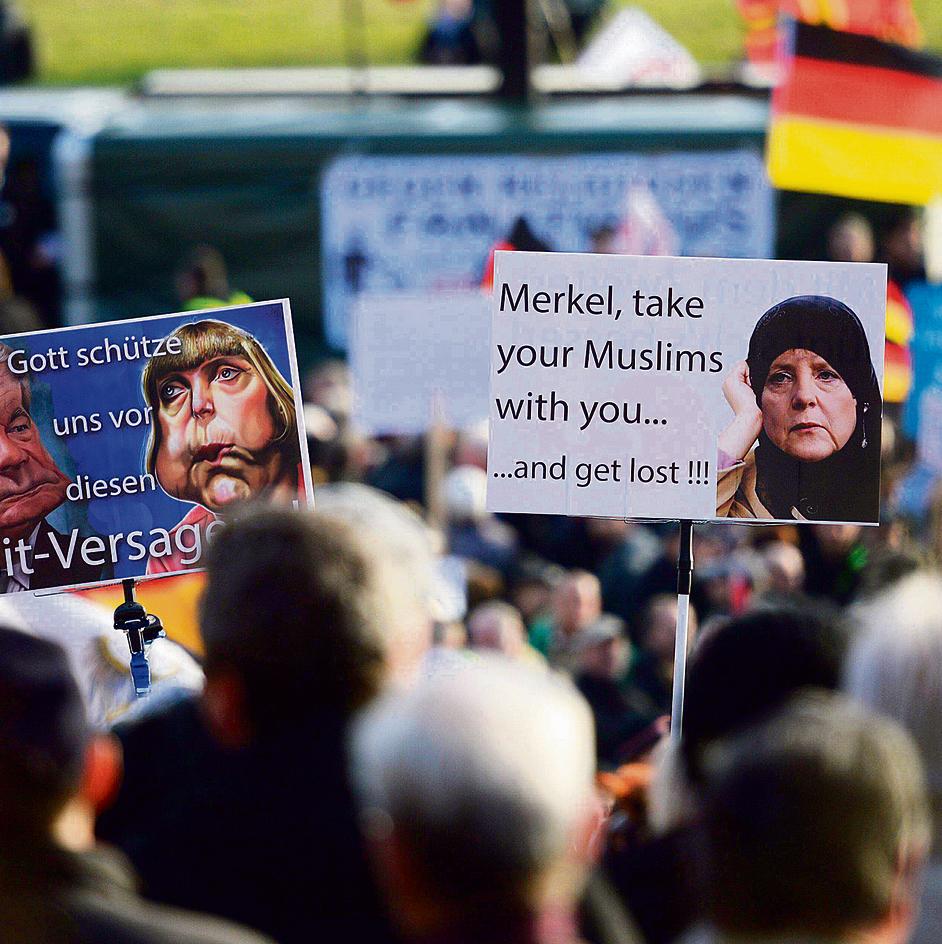 """הפגנה נגד מוסלמים בדרזדן, עם תמונת הקנצלרית מרקל ברעלה והכיתוב, """"קחי איתך את המוסלמים שלך ועופי"""""""