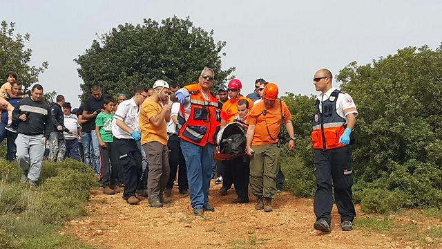 Search and rescue teams carry BG Amar's body from the scene