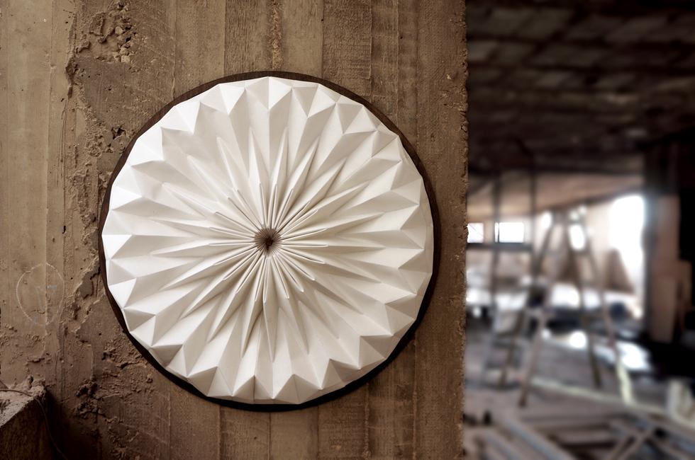 מנורת הקיר ''סהרא'' של סטודיו קאמידורו עשויה משי מוקשח בקיפול ידני שמרפרר לאוריגמי, בשילוב עץ, פליז ותאורת לד חסכנית בגוון חם (צילום: באדיבות צבע טרי)