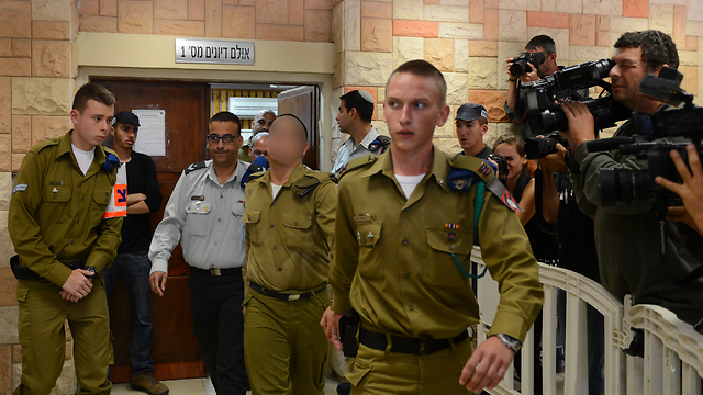 Court room with suspected soldier being led by military police (Photo: Avi Rokach)