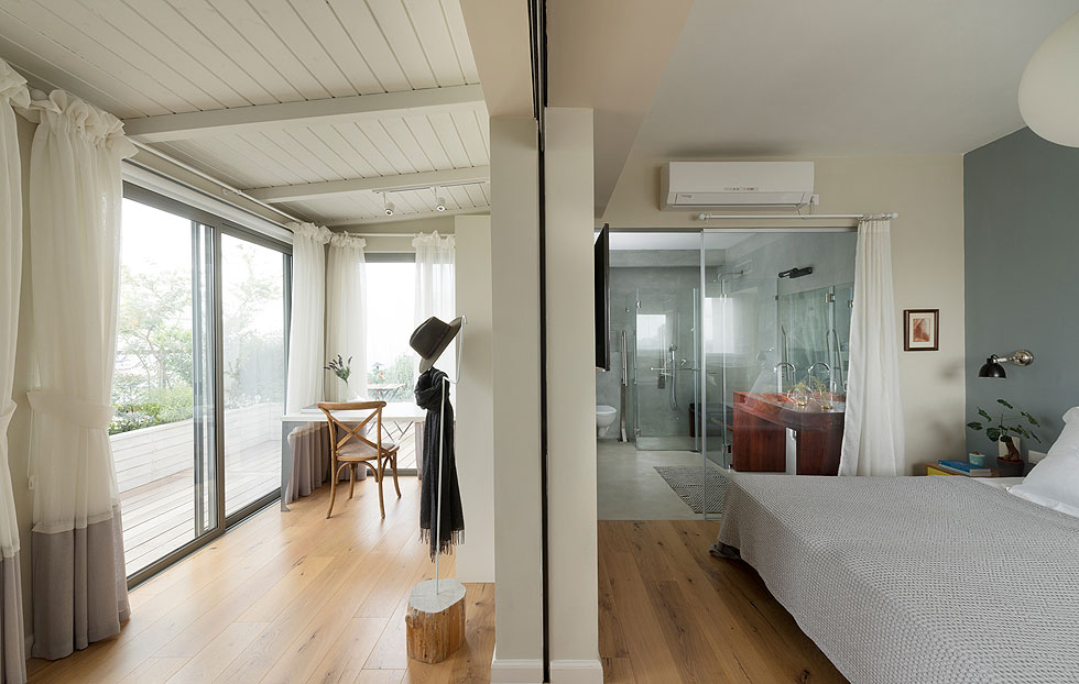 חדר השינה פונה למרפסת פרטית, והקיר שהפריד ביניהם הוחלף בקיר זכוכית. גם בין אזור המיטה לחדר הרחצה הצמוד מפריד קיר זכוכית, עם וילון (צילום: גדעון לוין)