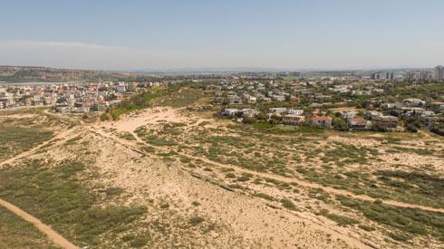 סוללת העפר שהקימו תושבי קיסריה בינם לבין ג'סר א-זרקא. תושביה חושבים שהמטרה העיקרית שלה היא לחסום את קו הראייה, ''כאילו שאם הם לא רואים אותנו, אנחנו לא קיימים'' (צילום: Take-Air)