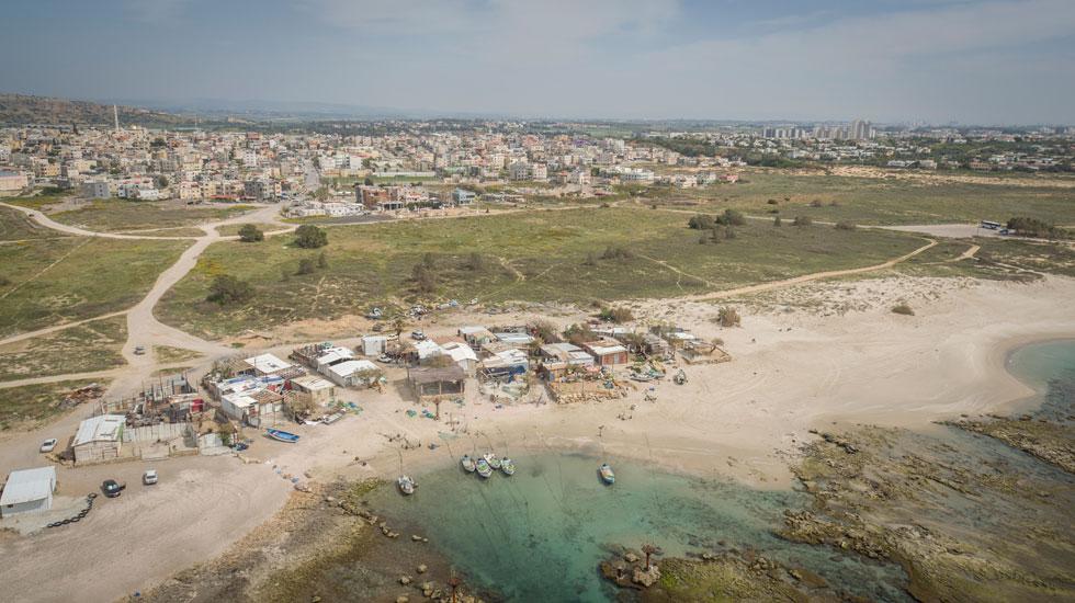מבט מהאוויר: על שפת הים כפר הדייגים של ג'סר א-זרקא, שבמסגרת התוכנית אמור לעבור שיקום והסדרה. הבנייה החדשה מיועדת ל-183 דונם מהשטח הירוק, שנמצא בבעלות המדינה ומפריד בין הים לבין היישוב ג'סר א-זרקא. כיום מתגוררים ביישוב 14 אלף איש, שמצטופפים ב-2,200 בתים (צילום: Take-Air)