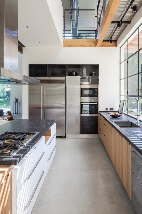 המטבח פתוח מלמעלה לכל גובה הבית. ליד המקרר ארון נירוסטה עם ידית תואמת (צילום: עמית גרון)