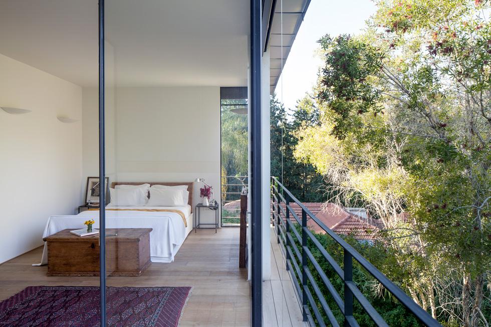בחדר השינה קיר חלונות ממוסגרים בפרופיל בלגי, מלווה במרפסת צרה (צילום: עמית גרון)