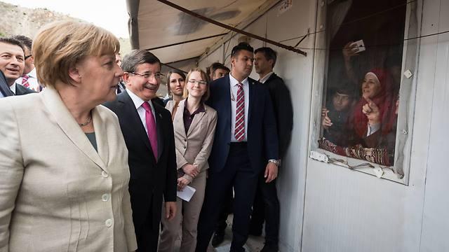 מרקל וראש הממשלה דבוטאולו מבקרים פליטים בטורקיה (צילום: Getty Images)