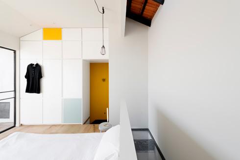 רצפת הזכוכית בגב המיטה. בדלתות הארון חוזרים הצהוב וגוון האקווה (צילום : גדעון לוין)