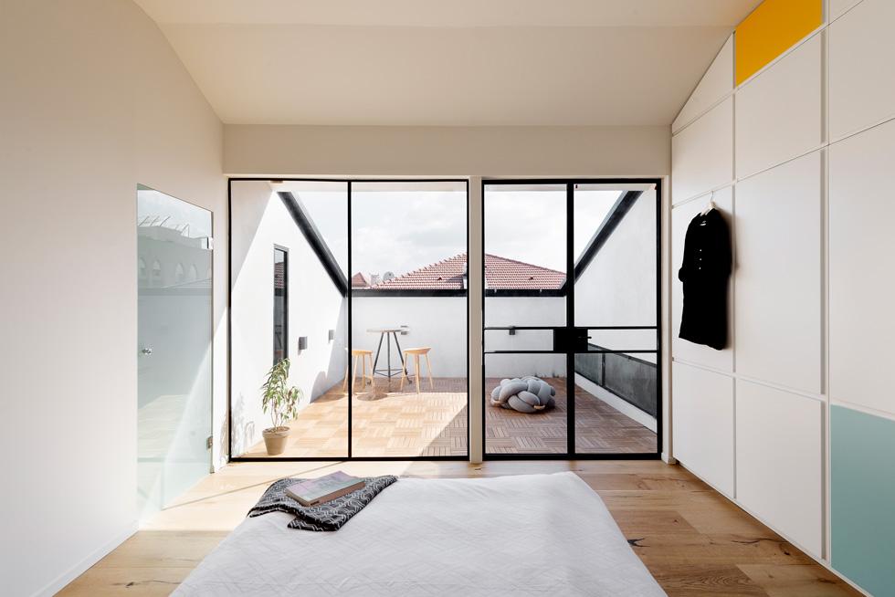 המיטה צופה אל המרפסת. משמאל חדרי הרחצה והשירות, ובמרפסת מימין החלון הנמוך שמאיר את הגלריה בפנים (צילום : גדעון לוין)