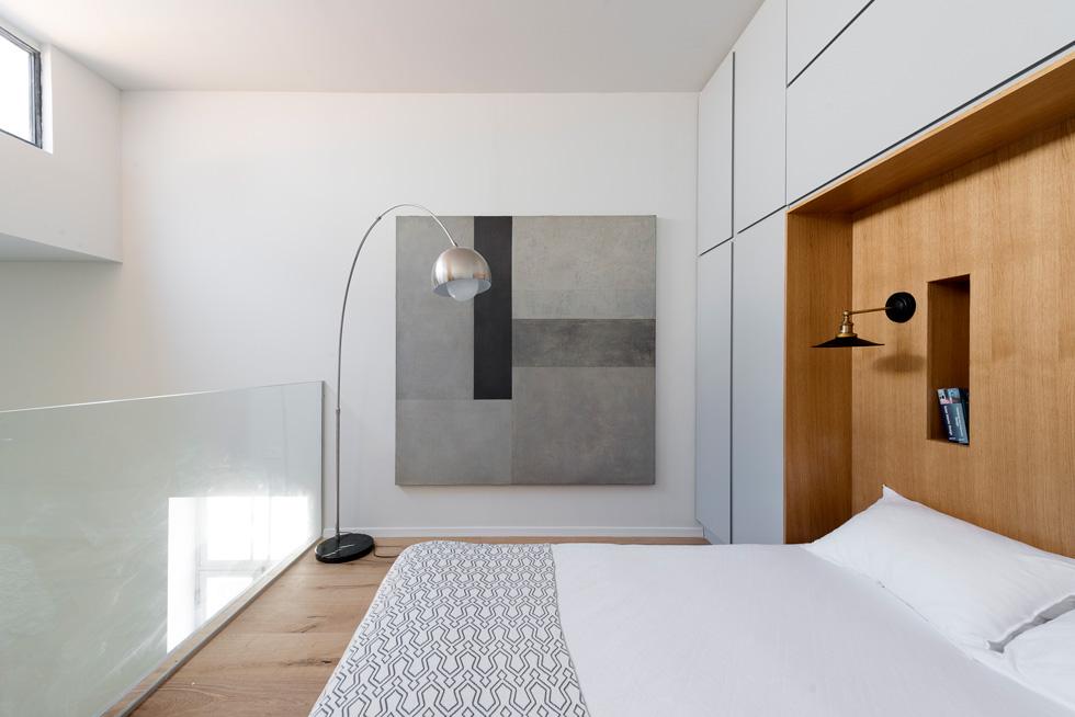 בגלריה ארון עם נישה מחופה פורניר עץ, שבה הוצבה מיטה. היא מוארת בזכות חלון רוחבי וצר שנפתח בקיר מולה (צילום : גדעון לוין)