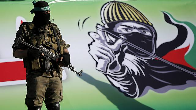 A Hamas militant standing before a Hamas poster (Photo: EPA)