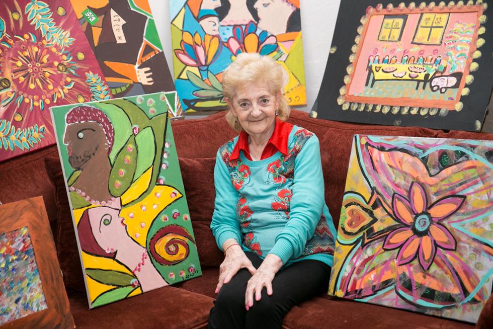 """ז'ני רוזנשטיין ויצירותיה. """"אני קוראת לציורים שלי 'קשקושים דמיוניים'. לפעמים אני מציירת תמונות משמחות, כמו פרחים, כדי להרגיש טוב יותר"""" (צילום: גילי לוינסון)"""