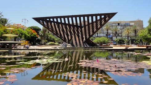 אחרי שיפוץ הכיכר, הבריכה והמזרקה ב-2011, הפסל נשקף בהיפוך במים. גן שעשועים (צילום: Lishay Shechter, cc)