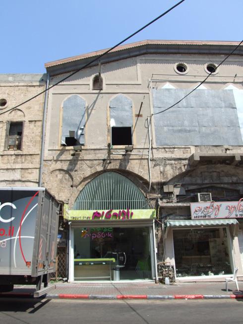 הבניין לפני השיפוץ: ללא משקופים ותריסים, נטול המרפסת התלויה המקורית, וללא זכר לחזית האבן האופיינית לרחוב (צילום: נאור מימר)