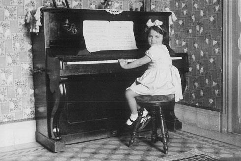 הילדה גבריאלה טוביאנה מנגנת בפסנתר של מסיכה. כיום נמצא הפסנתר בארץ (צילום: יואל שתרוג - אדמה יוצרת)