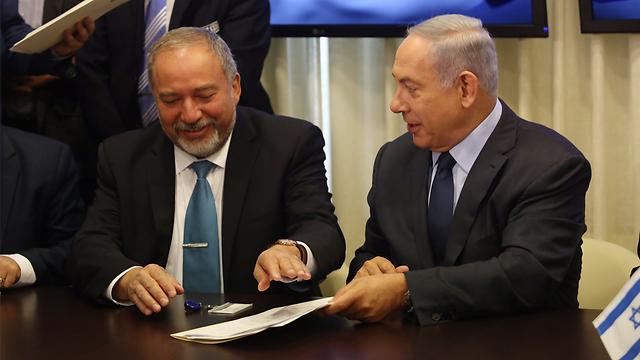 Lieberman and Netanyahu sign the coalition deal (Photo: Gil Yohanan)