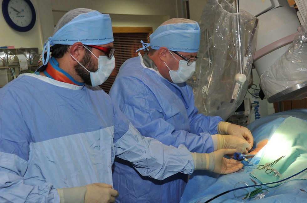 """בצילום : מימין: ד""""ר רון סלע, מנהל היחידה לאלקטרופיזיולוגיה וקוצבים במרכז הרפואי לגליל בנהריה, וד""""ר אלי חלפון, רופא בכיר במחלקה הקרדיולוגית. צילום: רוני אלברט, המרכז הרפואי לגליל (צילום: רוני אלברט – המרכז הרפואי לגליל) (צילום: רוני אלברט – המרכז הרפואי לגליל)"""