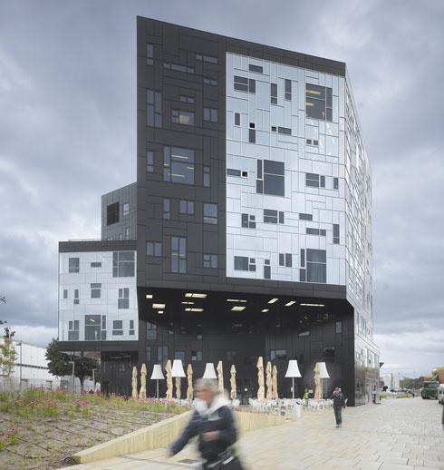 בנייןEXAC  באוניברסיטת וינה (2012) מחופה באלומיניום שחור שבו נפערו חלונות מרצדים, שחורים גם הם. את פינת הנפח מעטר קיר זכוכית ענק בגימור מראה, שמשקף את צבע השמיים והעננים. בכך שהבניין מגיב לסביבתו, הוא הופך ל''חי'' יותר (הדמיה: NO.MAD)