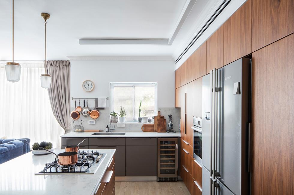 הארונות הגבוהים במטבח עשויים מפורניר עץ אגוז. שעון הקיר מיפן, קרשי החיתוך וסירי הנחושת משווקים בצרפת, והמנורות התלויות - וינטג' (צילום: אביעד בר נס)