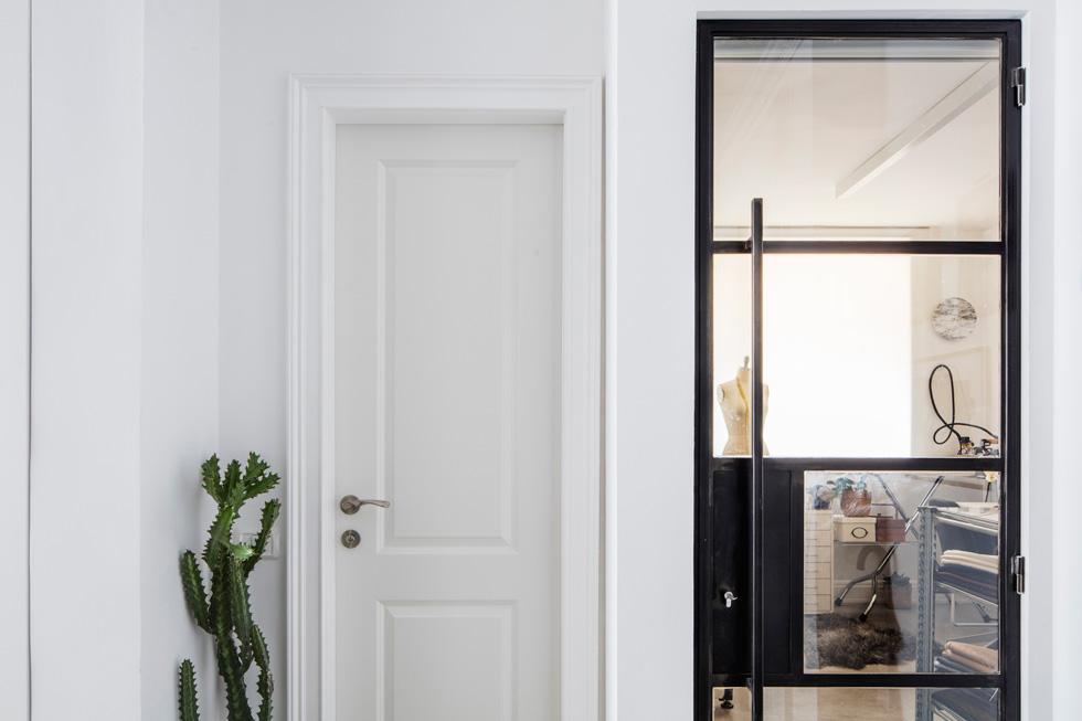 לצד דלת הכניסה שתי דלתות: האחת - שנפתחת לסטודיו של בעלת הבית - עשויה פרופיל ברזל בלגי שחור וזכוכית, והשנייה - של שירותי האורחים - קלאסית ולבנה (צילום: אביעד בר נס)