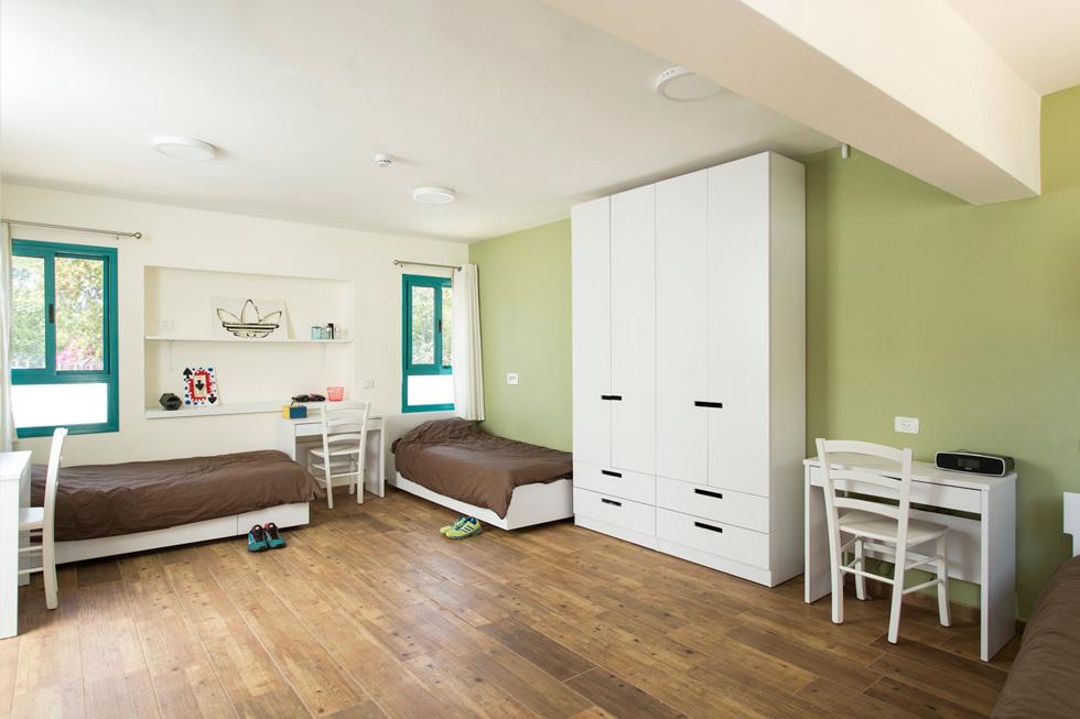 כל חדר מתוכנן למגורי שלושה. המעצבת התעקשה שכל אחד מהם יקבל ''חלקת עולם שכוללת מיטה, ארון, שולחן ומעליו כוורת, מנורת קריאה וחלון'' (צילום: רני לוריא)