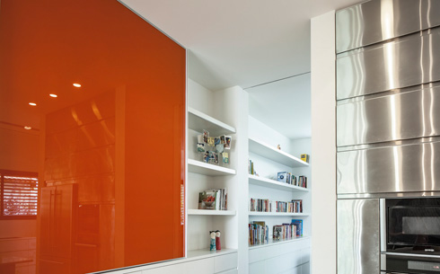 הספרייה הלבנה נמשכת אל חדר הטלוויזיה, הזכוכית הכתומה מסתירה פיר כביסה שיורד למרתף (צילום: עמית גרון)