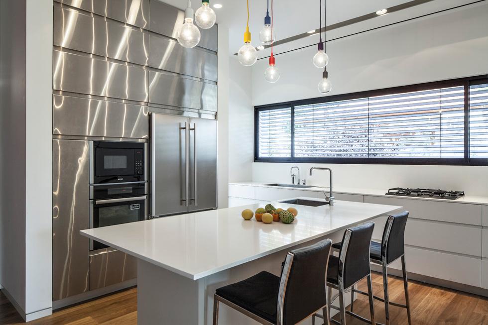 במטבח קיר יוצא דופן של ארונות גבוהים עם דלתות נירוסטה (צילום: עמית גרון)