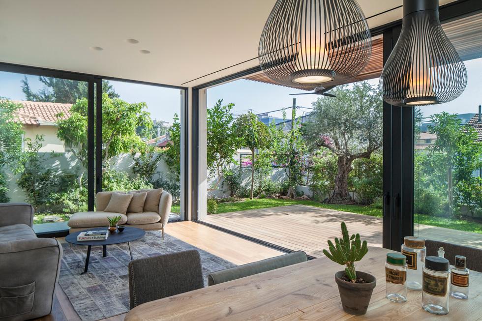 הסלון ופינת האוכל פונים אל החצר האחורית. עיצוב הפנים מבוסס על גוונים שקטים: לבן, עץ ואלמנטים שחורים (צילום: עמית גרון)