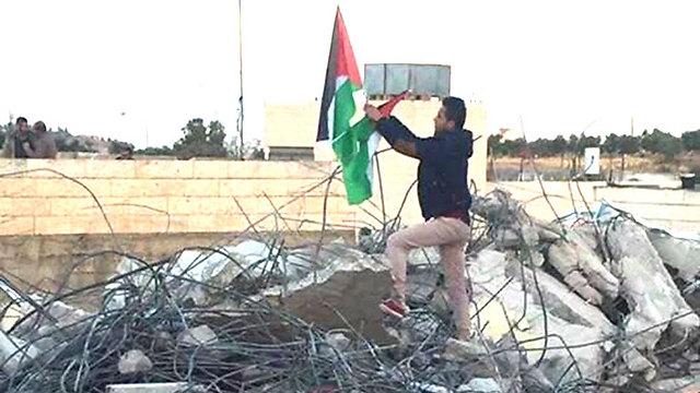 אחיו של המחבל תולה את דגל פלסטין על הריסות הבית, הבוקר ()