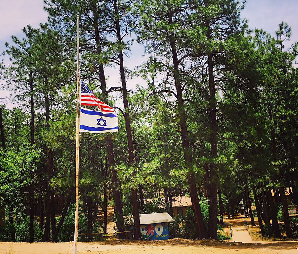 US and Israeli flags at half-staff at the girl's summer camp