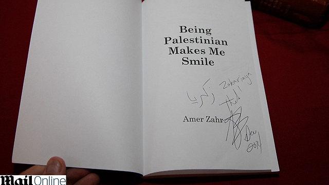 """עותק חתום של """"להיות פלסטיני גורם לי לחייך"""" של עמר זאהר (צילום: דיילי מייל) (צילום: דיילי מייל)"""