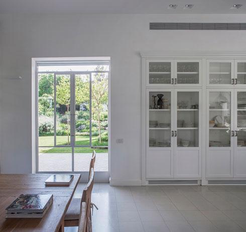 מבט מכיוון המבואה. ארון עם דלתות זכוכית תוכנן לכלי ההגשה (צילום: יואב גורין)