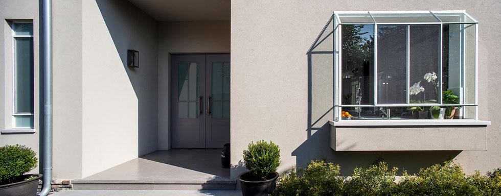 דלת הכניסה שקועה במבואה חיצונית מוצלת וקרירה, וחלון גדול בולט מהמטבח החוצה, כחממה קטנה (צילום: יואב גורין)