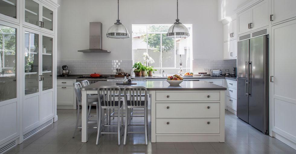 המטבח עוצב בסגנון כפרי בהיר. כל המנורות בבית מינימליסטיות, למעט השתיים שתלויות מעל האי (צילום: יואב גורין)