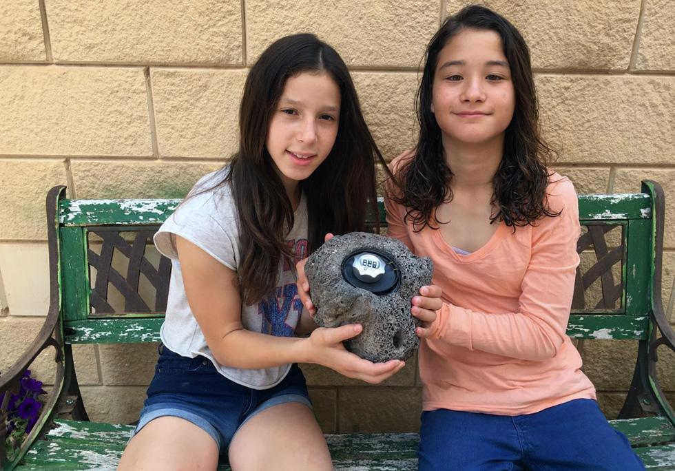 ליהי סנדלר ושני נהיר מציגות את ההמצאה שלהן: אבן שבתוכה מתחבאת כספת, להשארת המפתח מחוץ לדלת הבית. (צילום: יוגב ברגר)