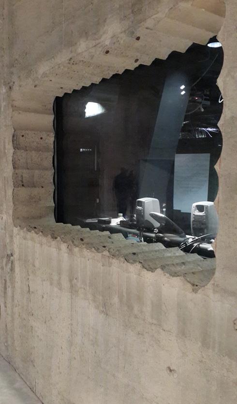 קיר הבטון המקורי בחלל מכלי הדלק התת-קרקעיים נקדח ליצירת פתח. סימני כוס היהלום שחצבה בבטון הושארו כביטוי אקספרסיבי לחומר (צילום: בועז רותם)