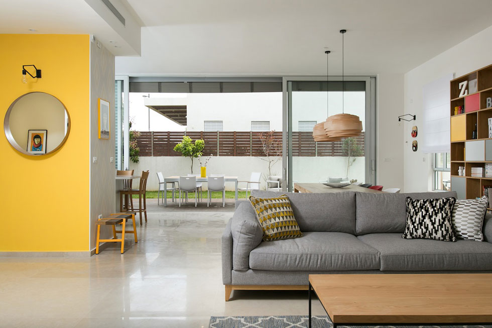 קיר המבואה, שמאחוריו המטבח, נצבע בצהוב. על החלק שפונה אל פינת האוכל הודבק טפט עם הדפס באפור וצהוב (צילום: שירן כרמל)