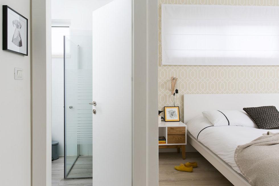חדר ההורים היה עירום, עם ארון ומיטה. כדי לרכך אותו נבחר טפט בהיר, וילון לבן מכסה את החלון ושידות צד הוזמנו מנגר (צילום: שירן כרמל)