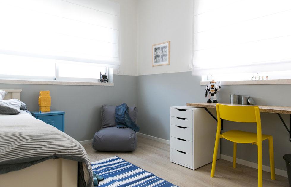חדרו של הבן, שעולה לכיתה א', עוצב בכחול-ג'ינס, אפור וצהוב. שליש מהקיר נצבע באפור, ומשטח OSB משמש כשולחן כתיבה (צילום: שירן כרמל)
