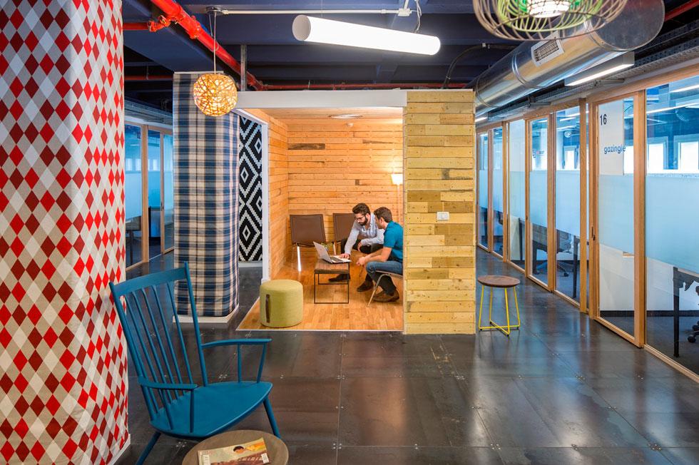 בין המשרדים תוכננו חדרי ישיבות קטנים, ברמת סגירות משתנה, שקירותיהם עשויים עץ-תפסנות גס. לצידם גם טריבונות מרופדות בכריות צבעוניות, המיועדות למפגשים בלתי פורמליים (צילום: שי אפשטיין)