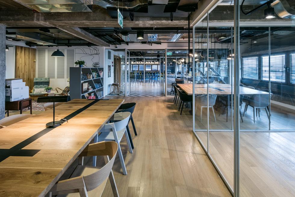 את החספוס התעשייתי של החלל מרכך הריהוט, המשלב בין כסאות משרדיים מסורתיים לכסאות עץ ושרפרפי בר של החברה הדנית MUUTO (צילום: עוזי פורת)
