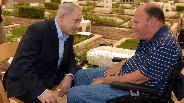 Hershko speaks to Prime Minister Benjamin Netanyahu, whose brother Yoni was killed in the same operation Hershko was wounded (Photo: Haim Tzah, GPO)
