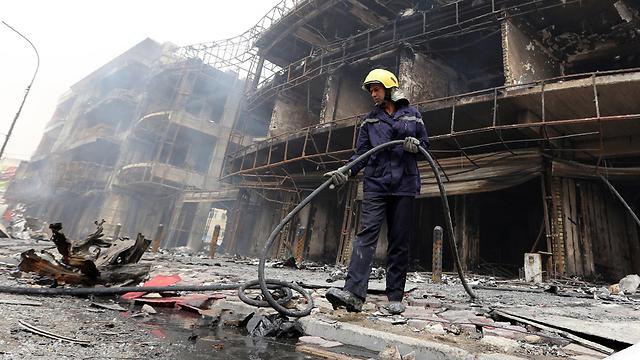 עדיין לא כיבו את כל הלהבות בגדד. כבאי בבגדד (צילום: AFP) (צילום: AFP)