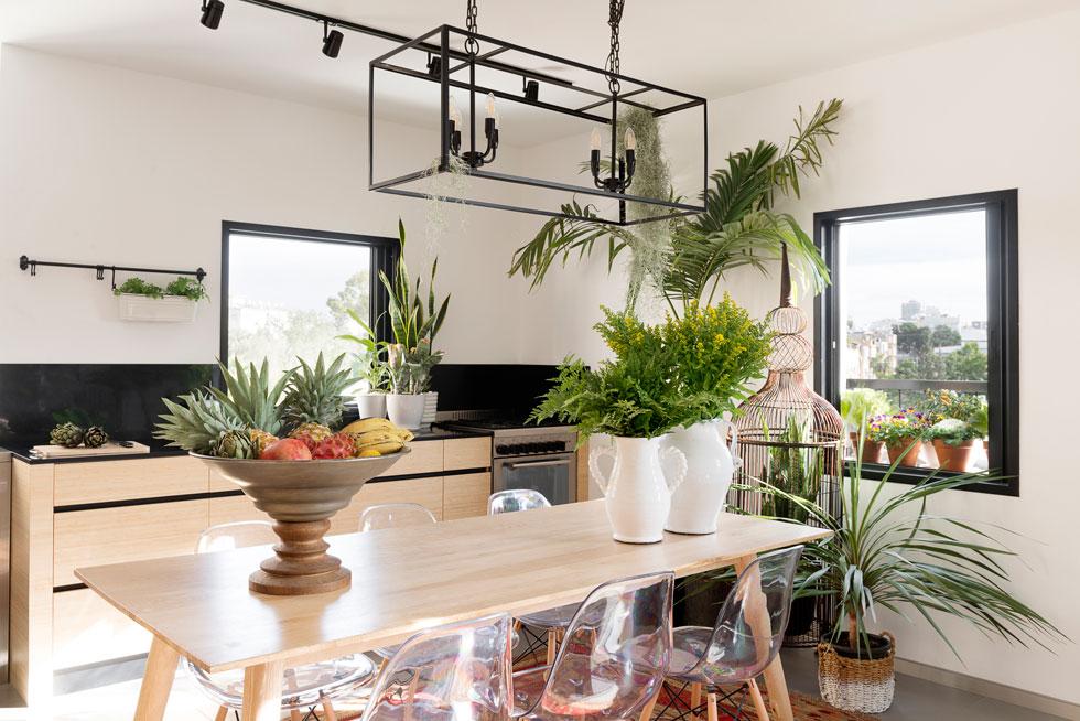 פינת האוכל כוללת שולחן מפלטת עץ דקיקה ומסביבו כיסאות שקופים. הכל טובל בירק (צילום: גדעון לוין)
