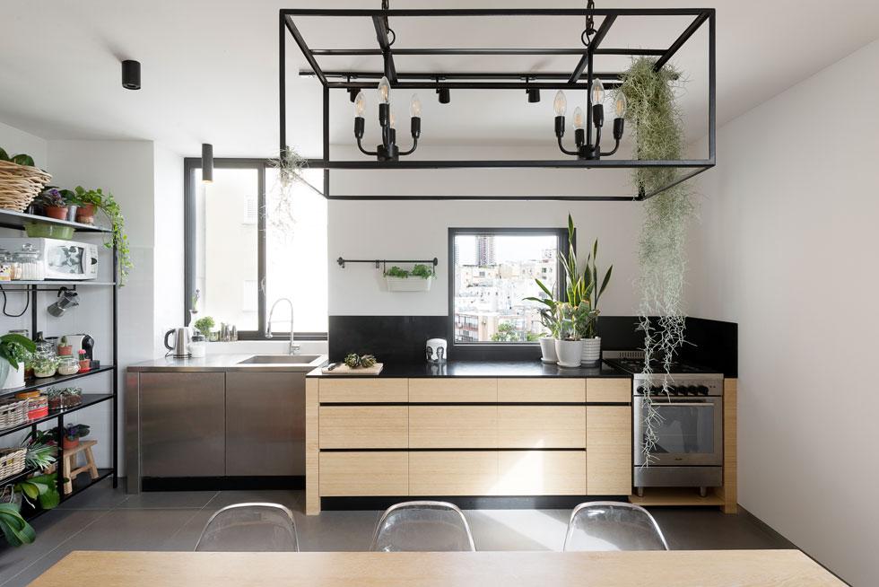ארונות נמוכים מבמבוק הורכבו מתחת לחלון המטבח. יחידת מדפים חופשית יוצרה בעבודת מסגרות. גוף תאורה טרנדי מברזל מאיר מלמעלה (צילום: גדעון לוין)