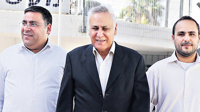 Former president Katsav on furlough from prison, flanked by his son Yisrael, to his left, and brother Lior, to his right (Photo: Shaul Golan)