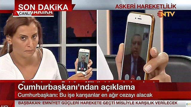 שבת, 00:34: ארדואן עולה לשידור ברשת NYV הטורקית מבעד למסך האייפון שמחזיקה המגישה באולפן וקורא לתומכיו לצאת לרחובות ולסכל את ההפיכה ()