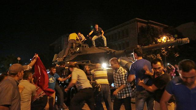 """01:35: דיווחים על עימותים בין אזרחים תומכי ארדואן לבין כוחות הצבא ועל עימותים ראשונים בין גורמים בכוחות הביטחון הנאמנים לנשיא לבין חיילים תומכי ההדחה של הממשלה. טנקים מקיפים את בניין הפרלמנט, ירי נשמע בנמל התעופה אטאטורק, גורמים באופוזיציה מביעים התנגדות לניסיון ההפיכה ומפקד הכוחות המיוחדים של טורקיה מכנה את הקושרים """"בוגדים"""" (צילום: AP) (צילום: AP)"""