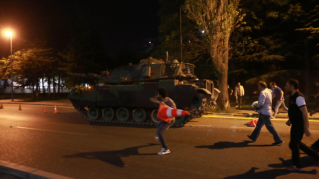 A man throws a traffic cone at a tank in Turkey (Photo: AFP)